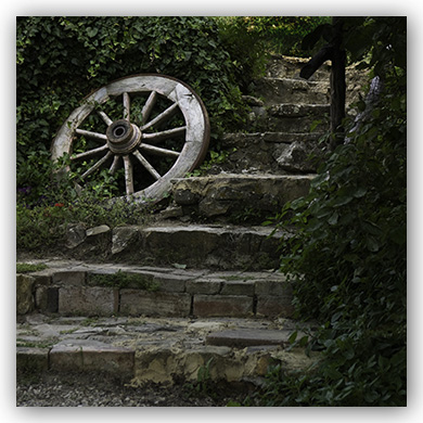 antique wagon wheel lying beside stone stairs